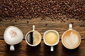 image of wooden table  - Variety of cups of coffee and coffee beans on old wooden table - JPG