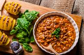 stock photo of scallion  - Spicy cowboy beans with chilli jalapeno scallions and bacon Hassleback Potatoe with herbs - JPG