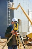 foto of theodolite  - Surveyor builder worker with theodolite transit equipment at construction site outdoors during surveying work - JPG