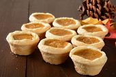 image of pumpkin pie  - Mini pumpkin pies on a rustic wooden table with holiday decorations - JPG