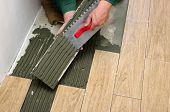 image of ceramic tile  - Man installs a ceramic tile  - JPG