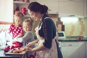 foto of little kids  - Mother with her 5 years old kids cooking holiday pie in the kitchen to Mothers day - JPG