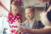 image of little kids  - Mother with her 5 years old kids cooking holiday pie in the kitchen - JPG