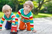 stock photo of daycare  - Two little siblings kid boys in colorful clothing with stripes playing with red school bus toy in summer garden on warm sunny day - JPG