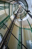 foto of spiral staircase  - Spiral staircase with lifter rails in the Cap Frehel lighthouse - JPG