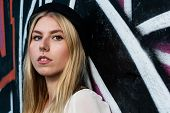 stock photo of nose piercing  - portrait of a young blonde girl with nose piercing and color graffiti background - JPG