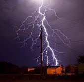 stock photo of utility pole  - Extremely detailed lightning bolt behind electric utility pole - JPG