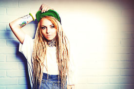 picture of dreadlock  - Modern teenage girl with blonde dreadlocks standing by the brick wall - JPG