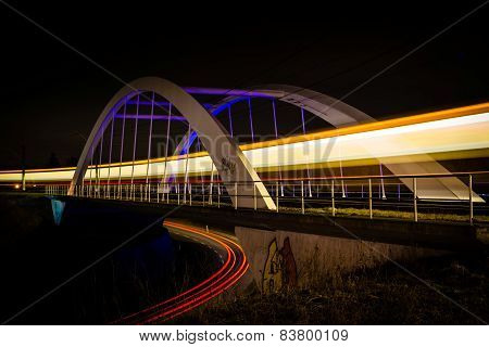 Railway bridge with train and car lights  at night