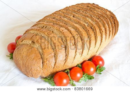 Loaf of sliced cornbread with tomatoes