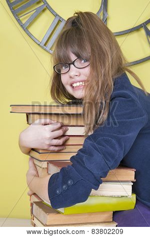 Girl In Glasses Hugging A Stack Of Books..