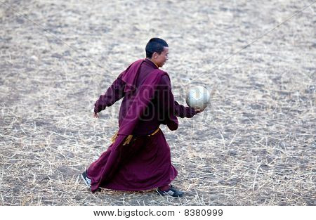 A Young Buddhist Monk With Ball