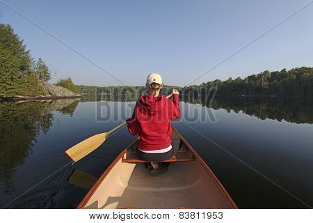 Woman Paddling A Canoe On A Northern Ontario Lake