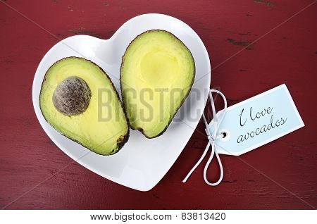 Avocado Cut In Half On Heart Shape Plate On Dark Red Vintage Rustic Wood Table, With I Love Avocados