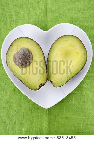 Avocado Cut In Half On Heart Shape Plate On Bright Green Tablecloth, Vertical.