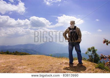 Man Traveler with Backpack on the top of mountain