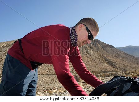 young Male Tourist In The Mountains Leaned Over To His Backpa