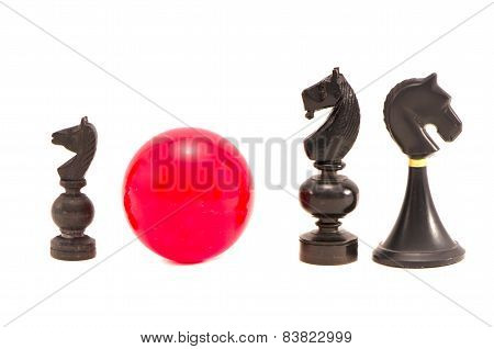Various Black Horse Chess  Pieces And Red Billiards Ball  Isolated