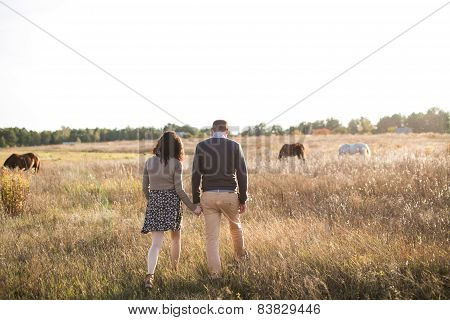 Young Couple Walks At Sunset Holding Hands