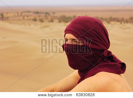 man with covered face  by red turban in desert