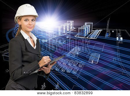 Businesswoman in helmet holding clipboard, smiling. Industrial zone as backdrop
