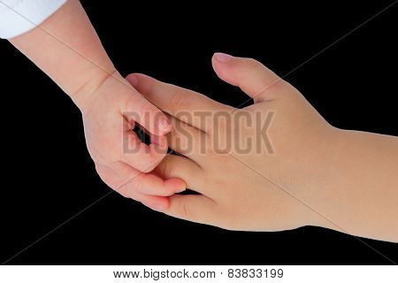 Hand of baby touching hand of child on black