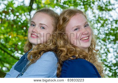 Two sisters heads together under tree