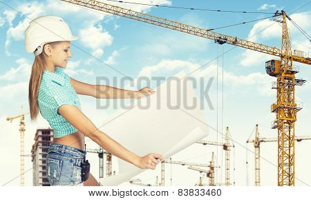 Woman in helmet standing half turn and holding paper sheet. Tower cranes as backdrop