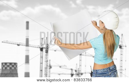 Woman in helmet standing backwards and holding paper sheet. Gray tower cranes as backdrop