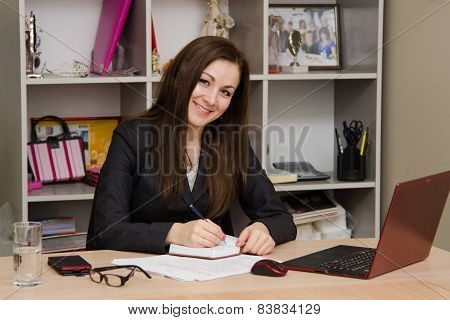 Female Office Worker With A Smile, Writing In Notebook