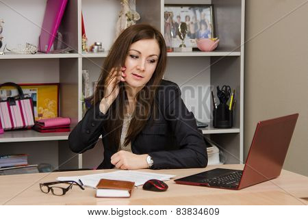 Business Woman In Office Talking On Phone Looking At Monitor