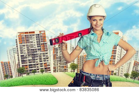 Woman in tool belt and helmet holding building level. Green hill, road, buildings as backdrop
