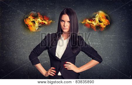 Angry woman standing with arms akimbo, fire from ears. Concrete wall in background