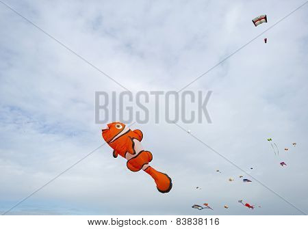 Colorful kites flying in a cloudy sky