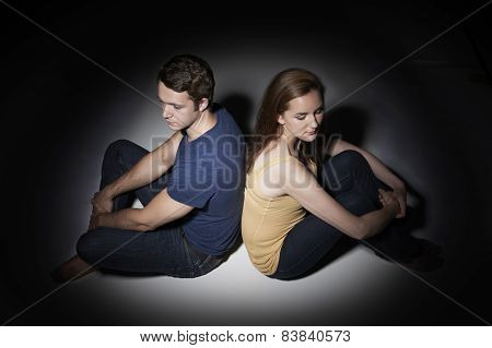 Unhappy Young Couple Sitting In Pool Of Light