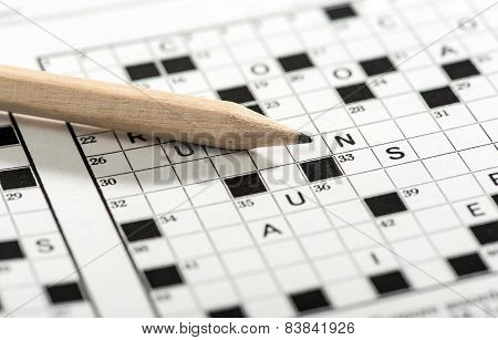 Conceptual Pencil On Top Of Crossword Puzzle Paper