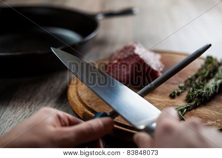 Sharpening the knife to cut the beef steak