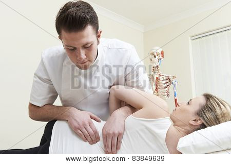 Male Osteopath Treating Female Patient With Back Problem
