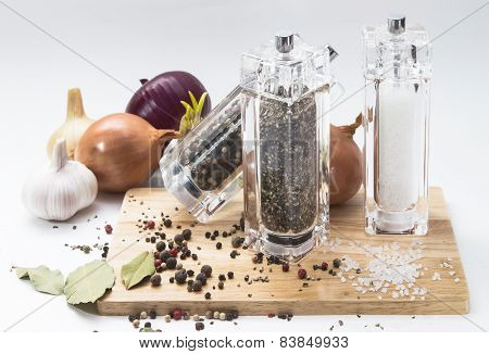 garlic, onions, glass mill with pepper and salt on a wooden Board, isolated