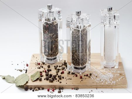 glass mill with pepper, salt and spices on a wooden Board, isolated