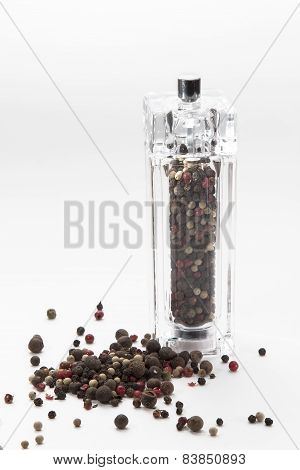 glass mill with color pepper peas isolated