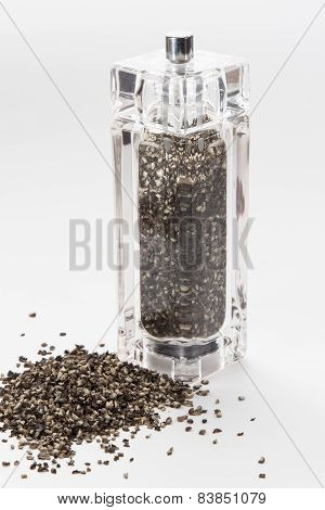 glass mill with black pepper peas isolated