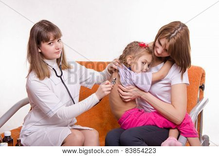 Children's Doctor Listening To Breathing Girl Sitting In Hands Of Mother