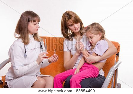 Pediatrician Holding A Syringe For Sick Child Sitting On Hands Of Mother