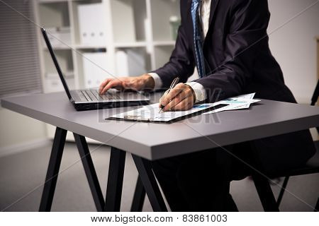 male hands doing paperwork with pen and laptop.