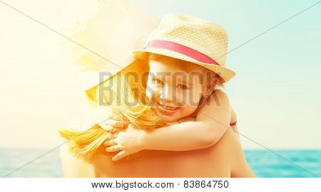 Happy Family On The Beach. Baby Girl Hugging Her Mother