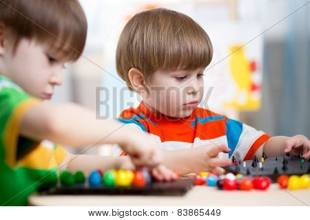 two kids brothers play together at table
