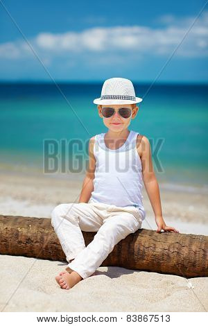 Stylish Kid Boy Sitting On Palm Tree At The Beach