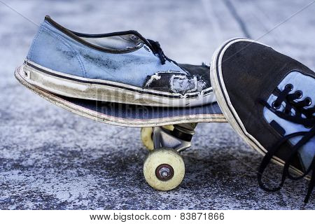 Pair Of Worn Out Sneakers On A Skateboard