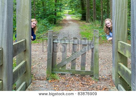 Two girls hiding at entry in nature